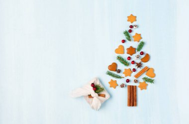 Christmas tree made of Xmas gingerbread cookies, cinnamons, cranberries and handmade furoshiki gift on blue background. Zero waste Christmas and New Year winter concept. Flat lay, copy space, top view