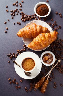 Fresh croissants  and cup of coffee on a table