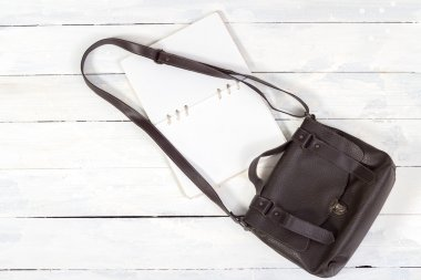 Leather bag with notebook on white wooden background