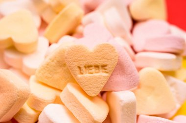 Word love written in German on a candy heart, sweet image for Valentine's Day.