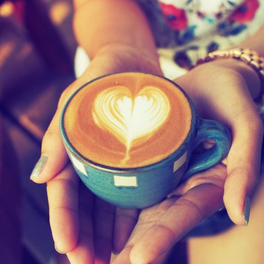 hand and cup of coffee latte art on the wood background vintage