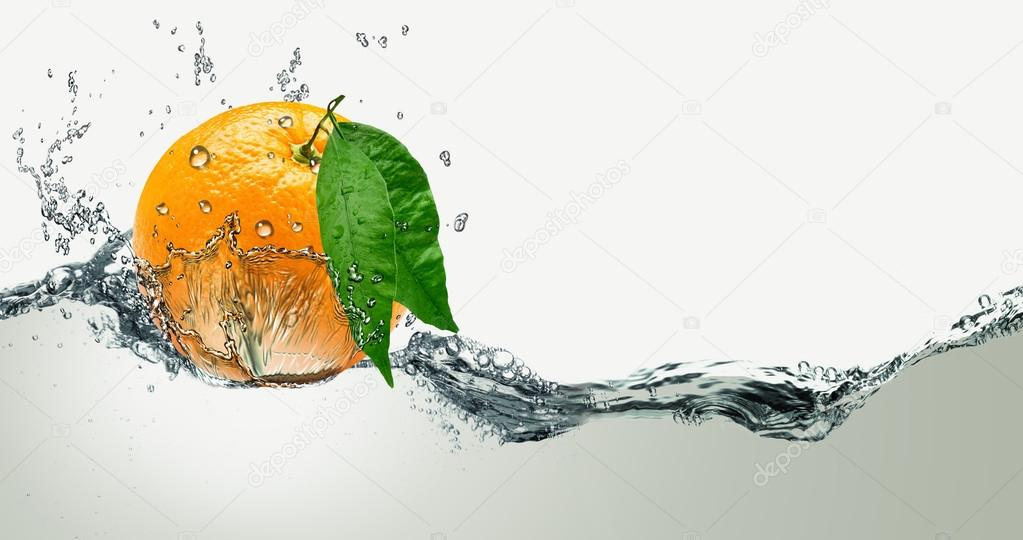 Juicy orange with green leaves on a background of splashing water.