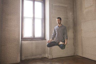 man levitating in yoga position