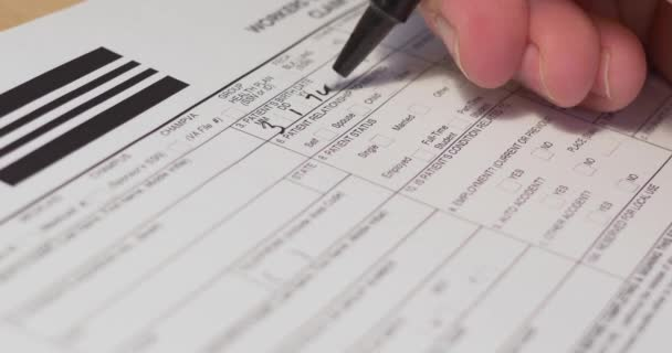 A slow dolly macro close-up shot filling out a generic workers compensation claim form. Data written are fictional.