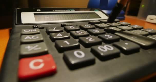 Close-up shot účetní zadávání čísel na kalkulačce s tužkou