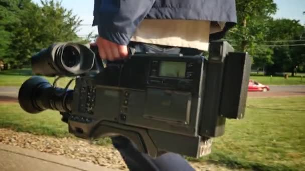 A low angle shot of a cameraman carrying his video camera to a production.