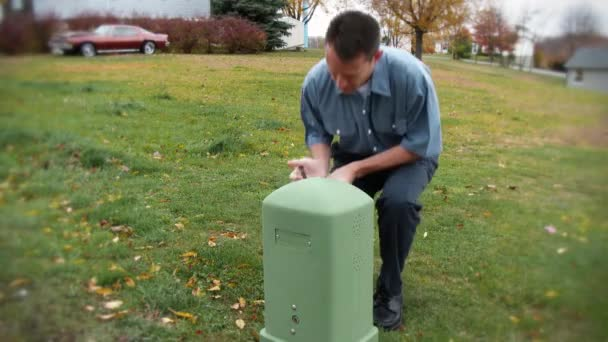 A utility worker inspects an exterior utility outlet.