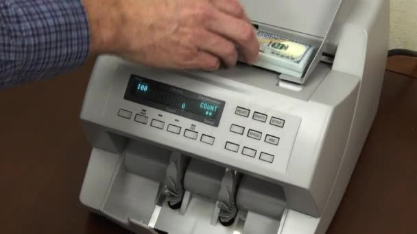 A money counting machine counts 10,000 dollars in new 100 dollar bills.