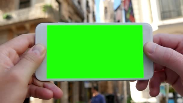 A man holds a smartphone with green screen