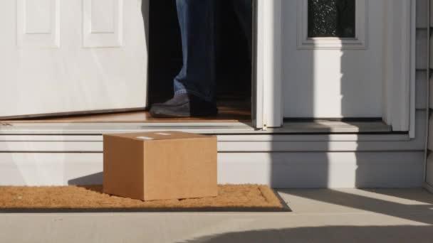 Muž zvedne balíček z před jeho domem