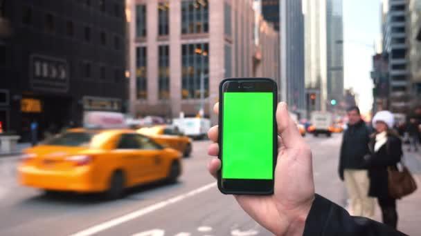 muž drží se zeleným plátnem smartphon