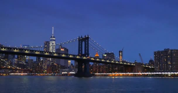 An evening establishing shot of the Brooklyn Bridge over the East River with lower Manhattan in the background.
