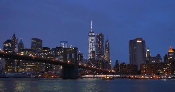 Večer na konci brooklynského mostu nad východní řekou s dolním Manhattan na pozadí.