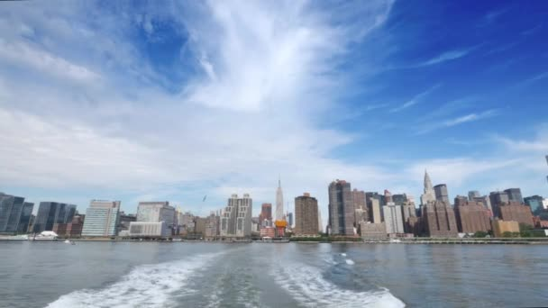 A daytime establishing shot of the skyline of midtown Manhattan as seen from the East River Ferry.
