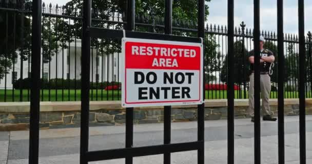 Hlídač stojí u brány před Bílým domem ve Washingtonu, DC