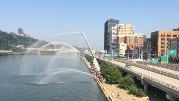 Firetrucks zobrazí sílu svých vodních trysek v Mon Wharf v Pittsburghu
