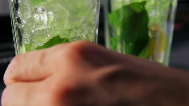 Barkeeper rührt Eis und Sirup in Glas