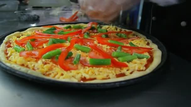 Dolly záběr uvedení papriky kuchaře na pizzu