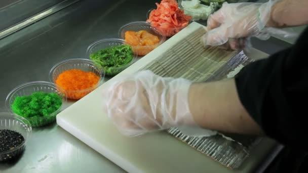 Šéfkuchař šíření tavený sýr a dá lososa při vaření sushi rolky
