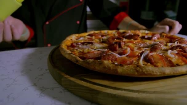 Pizzaiolo kropení oregano na pizza