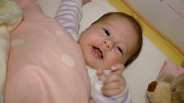 Dítě s úsměvem v postýlce
