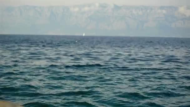 Vlny moře a hory v pozadí