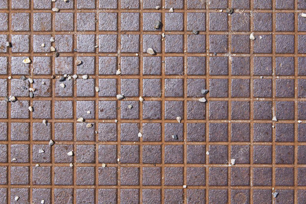 Superficie strutturata quadrato metallico arrugginito con ciottoli