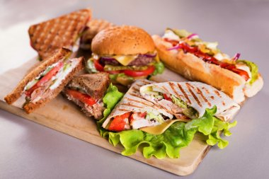 Fast food plate with burger hot dog sandwiches and chicken wrap