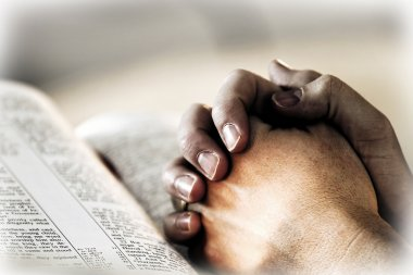 Praying Hands with Holy Bible and Light