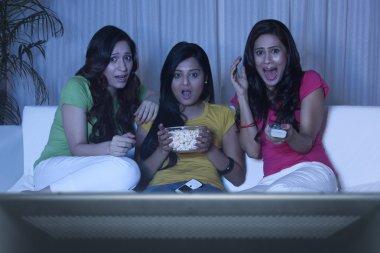Young women watching a horror movie