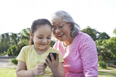 Grandmother and granddaughter using phone
