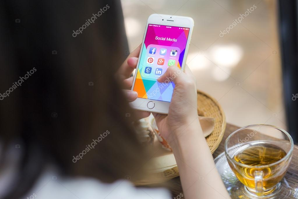 CHIANG MAI, THAILAND - JUNE 28, 2015: All of popular social media icons on smartphone device screen Apple iPhone 6 on woman hand in coffee shop cafe.