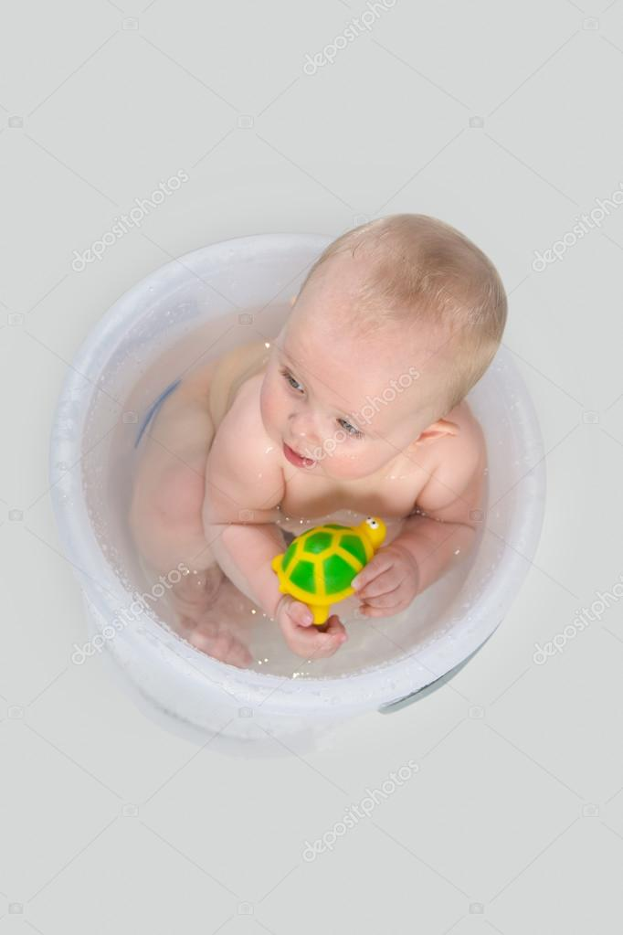 Cute Baby Having A Bath In Transparent Bucket And Playing With Toys ...