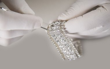 Man Hand with Gloves Putting Diamond on a Bracelet