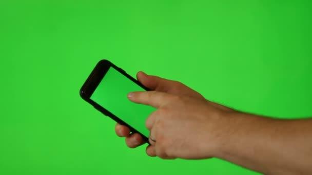 Ruka držící mobilní telefon s zelená obrazovka