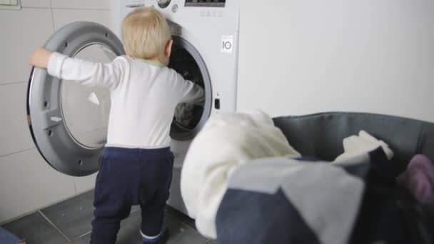 Two year old child doing household chores. Loading washing machine.