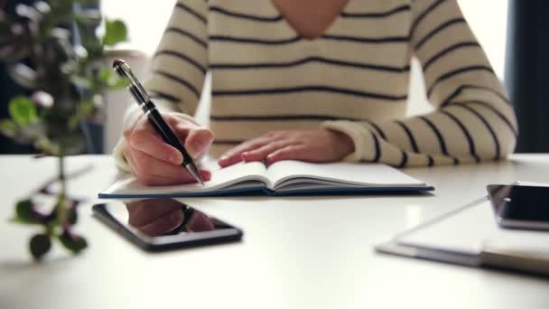 Egy üzletasszony tollal a füzetében. Munkahelyi okostelefonnal és táblagéppel az asztalon
