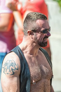 Muscular man with tatoos and leather at the Pride parade