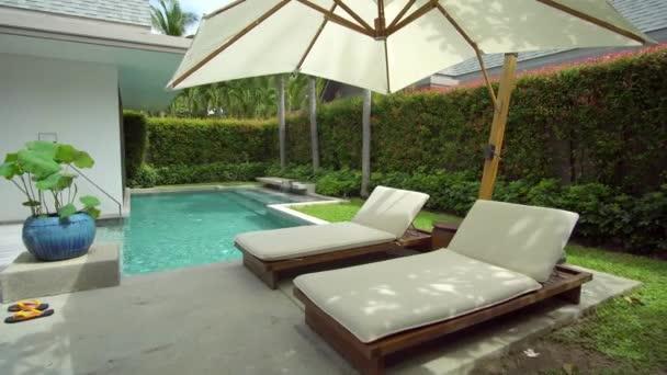 Weite Aufnahme von leeren Liegestühlen im Schwimmbadbereich, Schlafplätze in der Nähe