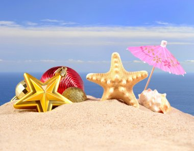 Christmas decorations seashells and starfish on a beach sand