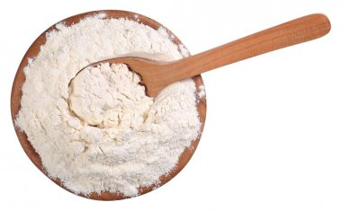 Top view of white flour in a wooden bowl with spoon on a white