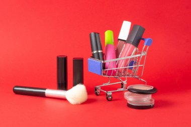 A set of lipstick cosmetics and lip glosses, powder, eyeshadow and a shopping trolley on a bright red background. The concept of buying cosmetics, online shopping, holiday