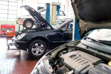 Three cars in a repair shop