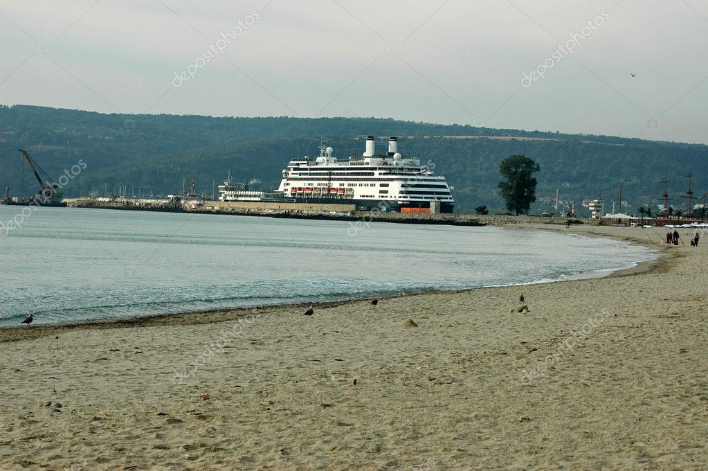 Sandy beach and waves shot against the coastline, in the port with liner, Varna, Bulgaria