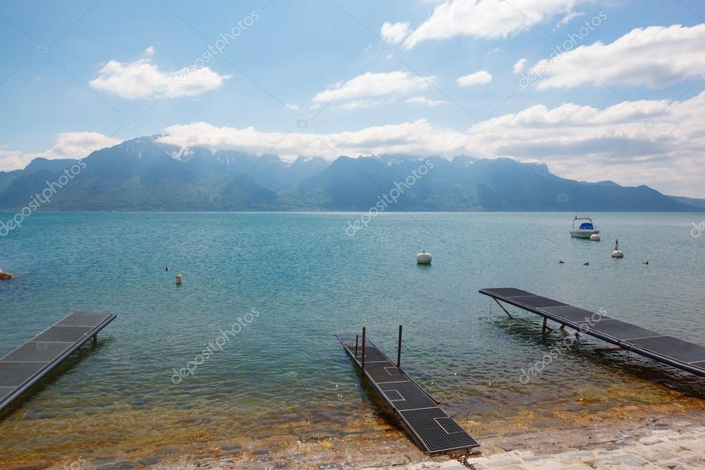 Landscape. Lakeside and snowy mountains at the sunny day