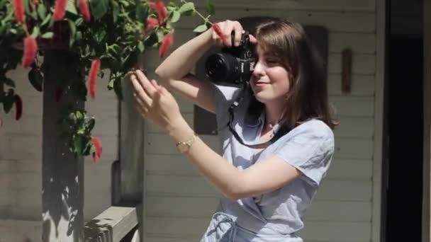 Egy nevető fiatal nő áll egy nyári kávézó ajtajában egy kamerával, és képeket készít egy érdekes növényről, miközben fogja a kezével. Előre nézz. Közepes terv