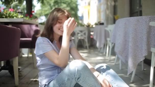 Egy gyönyörű fiatal lány világoskék blúzban és farmerban ül egy nyári kávézó padlóján és mosolyog, felhajtott fejjel. Közelkép. Előre nézz. Lassú mozgás.