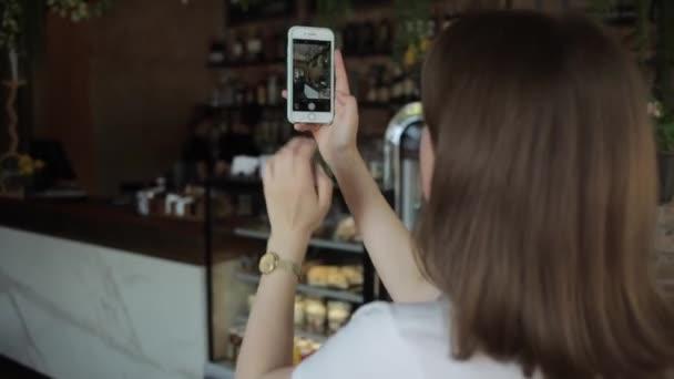 Misk, Weißrussland - 25. August 2020: Ein nettes junges Mädchen steht in der Caféhalle und fotografiert das Interieur mit einem Handy. Rückansicht. Nahaufnahme. Unscharfer Hintergrund. Fokus auf das Telefon