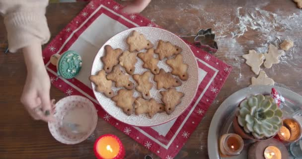A young girl cooking gingerbreads for Christmas and New Years and decorates figures of spruces and little men with glaze. View from above