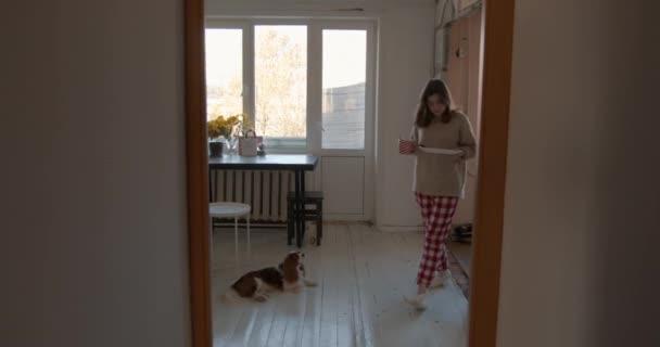 Egy csinos fiatal lány otthoni ruhában kijön a konyhából egy nagy tányérral és egy csészével a kezében, és a kutyája utána fut.